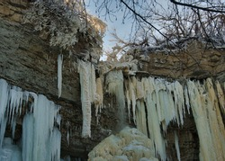 Inside the frozen Valaste waterfall, Estonia. Huge icicles hang on the limestone walls; unfrozen water is barely falling out of an ice crown in the center.