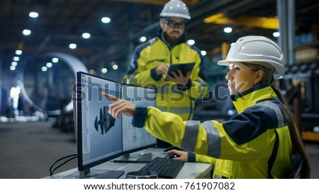 Inside the Heavy Industry, Factory Female Industrial Engineer Works on Personal Computer She Designs 3D Engine Model, Her Male Colleague Talks with Her and Uses Tablet Computer. Low Angle Shot. stock photo