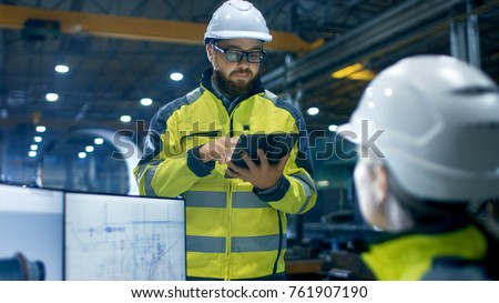 Inside the Heavy Industry Factory Female Industrial Engineer Works on Personal Computer She Designs 3D Engine Model, Her Male Boss Uses Tablet Computer. #761907190