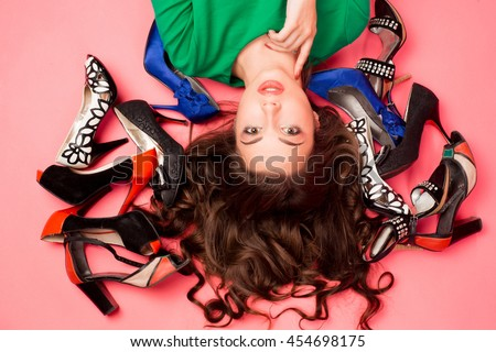 Inside the Studio portrait woman with gorgeous long dark hair among the shoes. A lot of fashionable different shoes around the girl\'s head, shopping, sale. Bright makeup, Studio background.