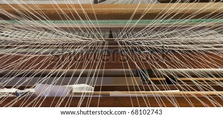 Inside the weaving machine, with the threads converging towards the inner of the machine