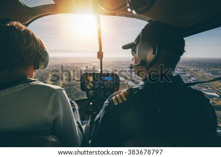 Inside view of a helicopter in flight, with man and woman pilots flying a helicopter on a sunny day.