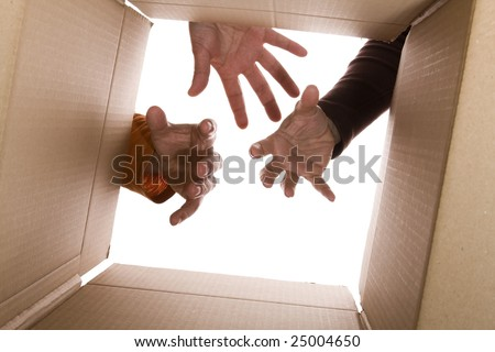 inside view of cardboard box with three hands trying to reach the content (selective focus)