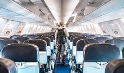 Inside view of commercial airplane with lonely man traveler - Emergency travel concept about flight delays and cancellations - Aerospace industry crisis with empty plane on bright azure filter