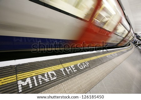 Inside view of London Underground Tube Station with Moving train, motion blurred.