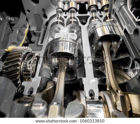 Inside view of modern engine, close up detail of two pistons in cylinder with four valves,some gears aside. #1060313810
