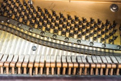 Inside view of old player piano: hammers, strings, tuning pegs, and metal sound board