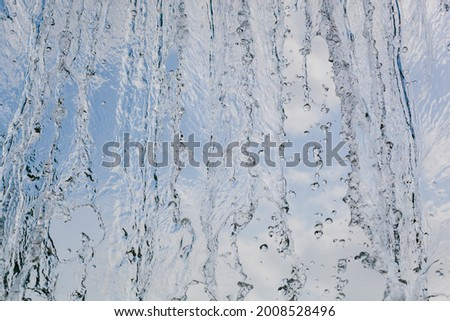 inside view of the falling water of the waterfall against the blue sky. beautiful texture of frozen water in motion. Foto stock ©