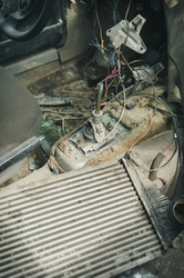 inside view to gear shifter and wires of a broken and disassembled interior of old abandoned car at dump
