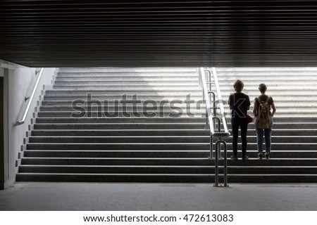 Insight into the future. Silhouette of young couple in the way out of underground. Urban scene with metaphorical relation to lifestyle, education or social issues.