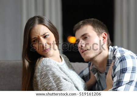 Insistent man trying to get sex and his worried girlfriend denying on a couch in the night at home