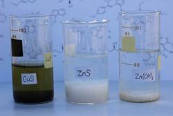 Insoluble precipitates in a beakers: black copper sulfide, white zinc sulfide and zinc hydroxide.