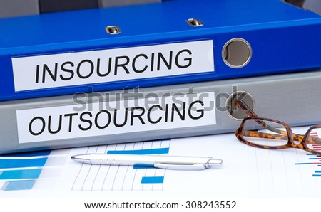 Insourcing and Outsourcing - two binders on desk in the office #308243552