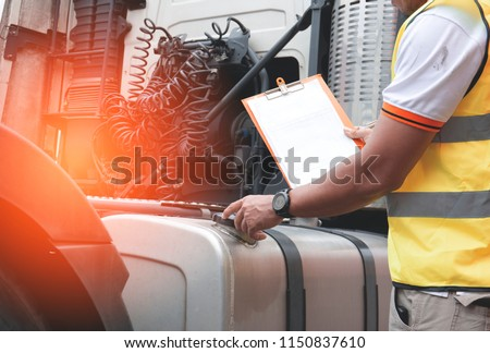 Inspecting truck safety.The truck driver is checking the truck's fuel tank.