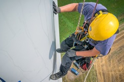 Inspection engineer rappels down a rotor blade of a wind turbine in a North German wind farm.