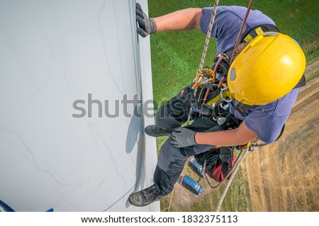 Inspection engineer rappels down a rotor blade of a wind turbine in a North German wind farm. Foto d'archivio ©