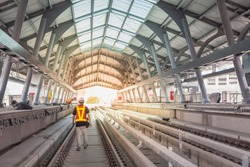 Inspector (Engineer) walk on viaduct of sky train in station area for check railway or track . Selective focus