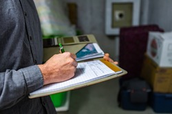 inspector holding a notebook in his hand during a home inspection in the basement, Close up and selective focus of a man taking professional notes.