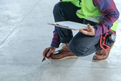 Inspector or engineer is checking and inspecting floor appearance and pointing to the surface. Inspection concept
