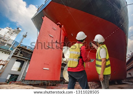 inspector, port controller, surveyor, foreman inspecting the final repairing of painting cleaning over hull dry dock of the commercial ocean ship, checking detail and report on line the progress works