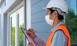 Inspectors or engineers are wearing an anti-virus mask and checking the building structure and the requirements of the wall paint. After the renovation is completed