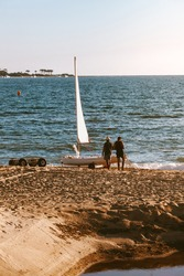 Inspiration and adventure. Meeting of friends on the beach. Planning the trip on the sailboat. Enjoying in an idyllic place.