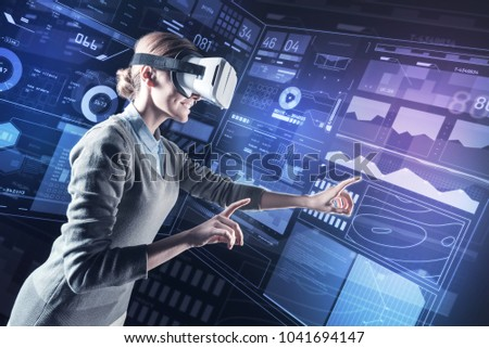 Inspiration. Cheerful young programmer smiling and pointing in front of herself while getting inspiration for her work in virtual reality