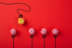 Inspiration concept crumpled paper light bulb metaphor for good idea on red background