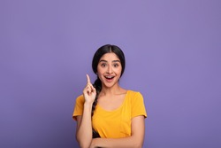 Inspiration, Creativity, Solution, Eureka concept. Portrait of excited young indian woman in yellow t-shirt raising finger up and smiling, having wow creative idea, purple studio background, copyspace