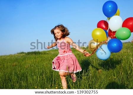 inspiration, happy little girl jumping outdoors with balloons
