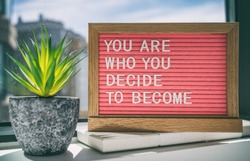 Inspiration quote message sign saying You are who you decide to become - life advice for self esteem, confidence. Home background.
