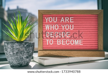Inspiration quote message sign saying You are who you decide to become - life advice for self esteem, confidence. Home background. Stock foto ©