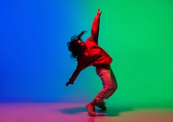Inspiration. Stylish sportive girl dancing hip-hop in stylish clothes on colorful background at dance hall in neon light. Youth culture, movement, style and fashion, action. Fashionable bright