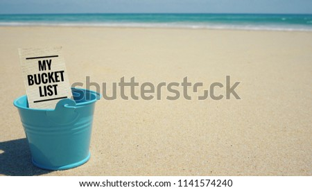 Inspirational and conceptual - 'My bucket list ' written on a white paper inside of a blue bucket. With vintage styled background.