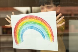 Inspirational little kid holding a drawing of a rainbow through the window