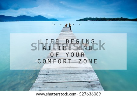 Inspirational motivating quote on long exposure of wooden jetty at sea facing island with cloud and sky at twilight. life begins at the end of your comfort zone #527636089