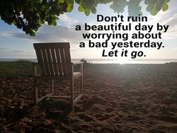 Inspirational motivational quote - Don't ruin a beautiful day by worrying about a bad yesterday. Let it go. With empty chair under the shady tree on the beach against bright sky sunlight over horizon.