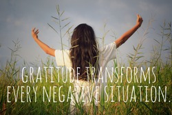 Inspirational motivational quote - Gratitude transforms every negative situation. With young woman in the field, standing alone with raised hands and open arms against the gloomy blue sky background.