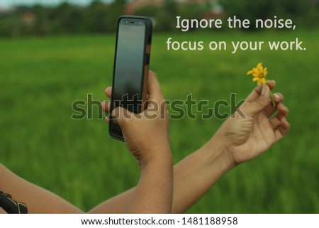 Inspirational motivational quote - Ignore the noise, focus on your work. With smartphone photographer at work creating concept with flowers. Words of wisdom concept.