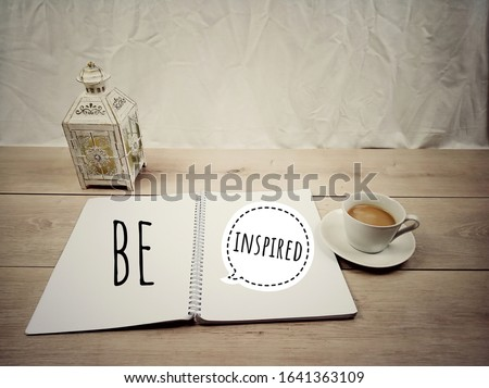 Inspirational quote - Be inspired. With a cup of white coffee, classic light  lantern and  notes on spiral white notebook on wooden table background. Single word of motivational quotes, flat lay. Stock photo ©