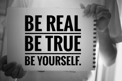 Inspirational quote - Be real. Be true. Be yourself. With young girl holding white paper book sign with reminder notes. Self confident motivational words concept in black and white background.