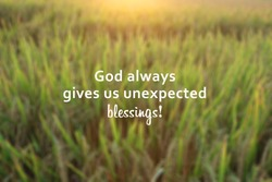 Inspirational quote - God always gives us unexpected blessings. With blurry background of dreamy morning sunrise light over the field. Believe in God concept.