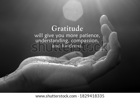 Inspirational quote - Gratitude will give you more patience, understanding, compassion, and kindness. With open palm hand receiving the light concept on black and white abstract art background.