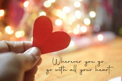 Inspirational quote - Wherever you go, go with all your heart. On pink, yellow and white bokeh light background with hand holding red love paper shape. Believe in your heart intuition concept.