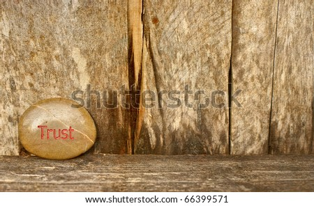 """Inspirational stone with the word """"trust"""" engraved on it on a rustic wood backdrop with copy space.  Grunge textured."""