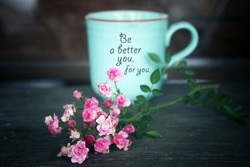 Inspirational words - Be a better you, for you. Self care and love motivational quote written on a green cup of morning coffee or tea with little pink roses on the table vintage background.