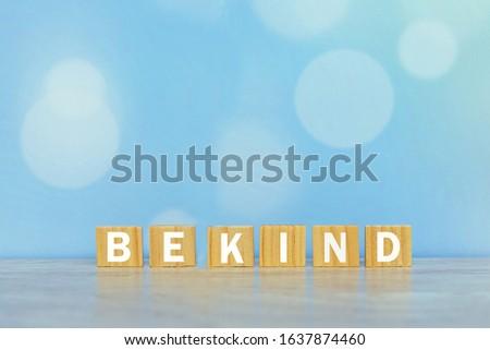 Inspirational words on wooden blocks - Be kind. On vintage soft blue bokeh background. Kindness motivational quote concept.