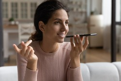 Inspired by innovations. Happy young hispanic woman sit on couch speak to phone ai give audio command search answer on question online. Confident millennial lady send vocal message using voicemail app