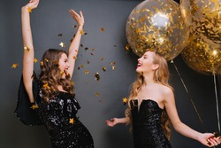 Inspired curly pale woman singing with hands up on dark background. Romantic blonde girl in black outfit holding party balloons and looking at friend which dancing under confetti.