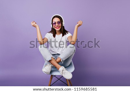 Inspired dark-haired girl sitting on chair and laughing on purple background. Indoor photo of smiling amazing female model in white clothes and headphones.